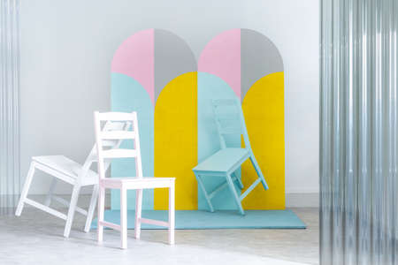 Pastel chairs and geometric screen in bright studio interior with white walls. Real photo
