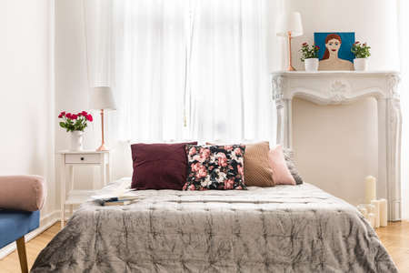 Chic bedroom interior featuring a bed with multicolor cushions and a velvet throw and white ornamented fireplace mantel as a decoration. Real photo.