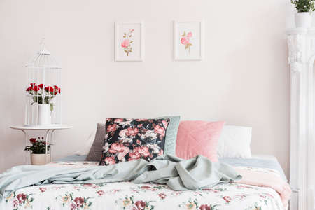 Close-up of flower pattern bed cover and pillows on a bed which is standing against a light color wall with rose illustrations in a feminine classic bedroom interior. Real photo.