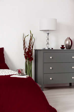 Grey commode with a lamp and a vase next to a flower and bed in a luxurious hotel room interior