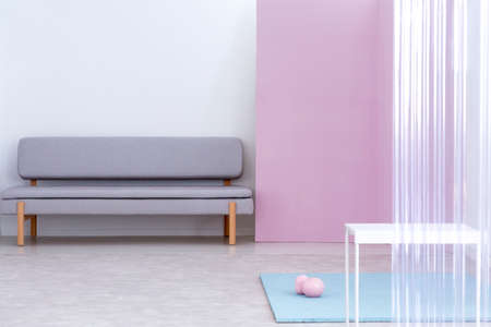 Real photo of a gray sofa standing in a simple living room interior with pink wall and white, metal table