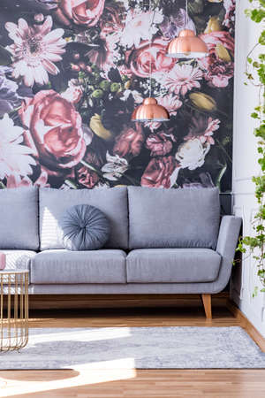 Grey sofa against flowers wallpaper in feminine living room interior with rug. Real photo Stock fotó