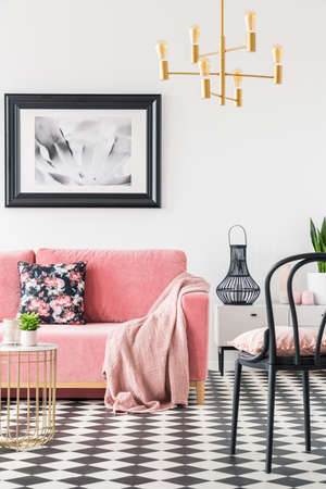 Black chair near pink couch in modern living room interior with poster and gold lamp. Real photo Imagens