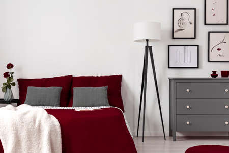 Red sheets on a bed, lamp and chest of drawers in a bedroom interior. Real photo. Empty wall, place your graphic