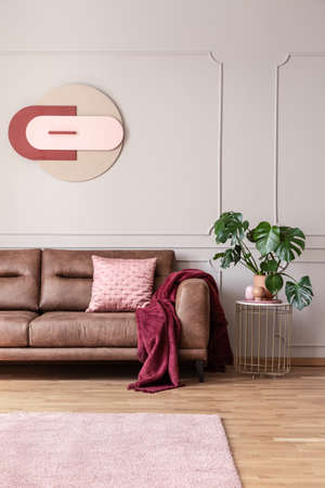 Poster above leather sofa in bright living room interior with carpet and plant on table. Real photo Stock Photo