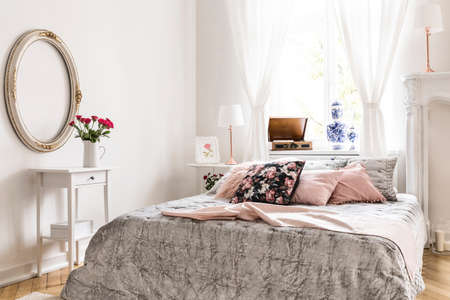 English style bedroom interior featuring a bed with light gray bedding and lemonade pink and rose pattern pillows and white ornamented furniture and decorations. Real photo