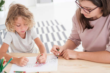 Little kid drawing a house using colorful crayons with his female, therapist during a meeting in the office Stock Photo