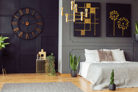 Black clock, golden chandelier, paintings and white bed in an elegant bedroom interior. Real photo
