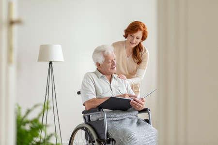 Nurse taking care of a man in a wheelchair in a nursing home