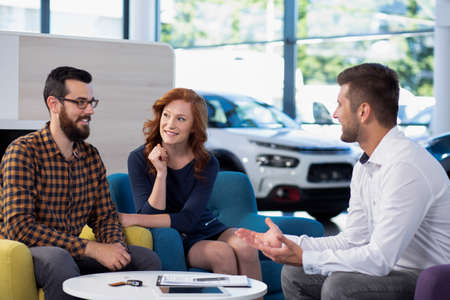Married couple talking to a car dealer in a showroom