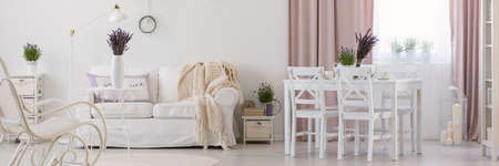 Panorama of white apartment interior with chairs at dining table next to sofa with blanket. Real photo Stock fotó