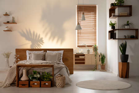 Real photo of a bedroom interior with wooden accents, bed and aflower shadow on the wall Archivio Fotografico - 107877570