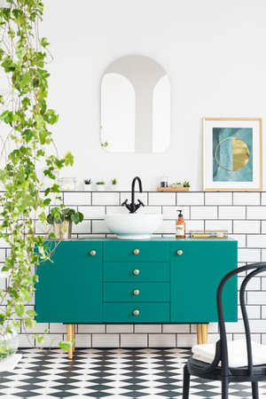 Mirror and poster above green cabinet in bathroom interior with black chair and plants. Real photo Archivio Fotografico