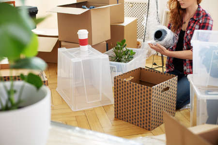 Woman protecting vase with foil while packing stuff into boxes after relocation