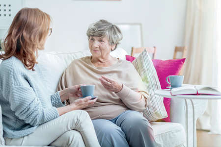 Smiling grandmother talking with friendly caregiver during meeting at home Stock Photo