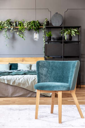 Blue armchair on white carpet in grey bedroom interior with wooden bed and plants. Real photo