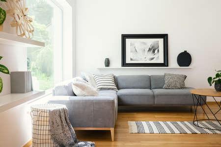 Zwart-wit textiel en decoraties in een klassiek woonkamerinterieur in Scandinavische stijl met houten meubels en natuurlijk zonlicht