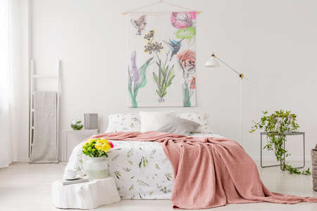 A bunch of yellow fresh cut flowers in a bright bedroom interior with a bed dressed in white linen and peach blanket. Fabric on the wall above the bed. Real photo.