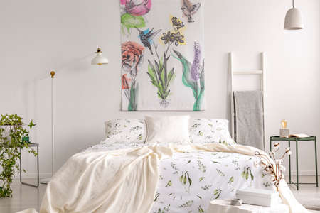Wall art of flowers and birds painted on a fabric above a bed which is dressed in green plants pattern on white bedding in a fresh looking bedroom interior. Real photo. 스톡 콘텐츠 - 107950096