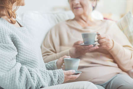 Senior women drinking tea during conversation in a nursing house
