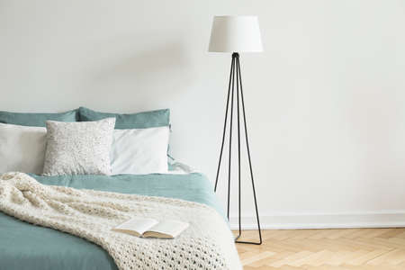 Minimal and simple white wall and parquet bedroom interior with a bed and a lamp. Empty space. Real photo.