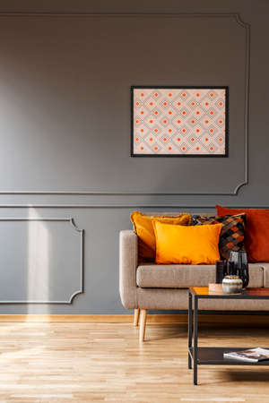 Mock-up poster with pattern on a gray wall and orange cushions on an elegant sofa in a fancy living room interior with copy space place for a floor lamp. Real photo.