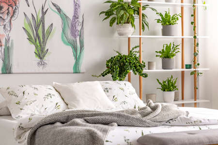 Urban jungle bedroom interior with plants in pots beside a bed dressed in organic cotton linen of white color with green print. Real photo.