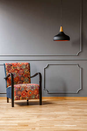 Sillón vintage con un colorido patrón de estilo boho y una luz de techo negra en un elegante salón gris con espacio para copiar y espacio para un gabinete. Foto real. Foto de archivo