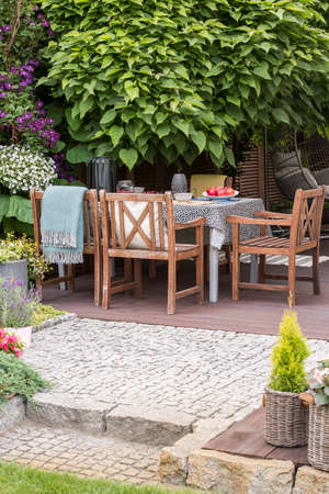 Wooden chairs at table on terrace with flowers and trees in the garden