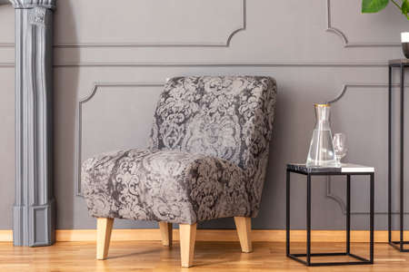 Table next to patterned grey armchair against wall with molding in living room interior. Real photo
