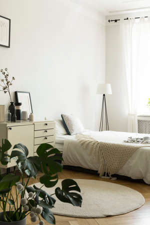 A monochromatic womans bedroom interior with white and beige furniture, like a bed and a drawer cabinet. Copy space wall. Real photo.