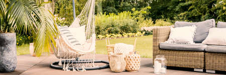 Lanterns and basket between rattan sofa and hammock with pillows in the garden. Real photo Stock fotó