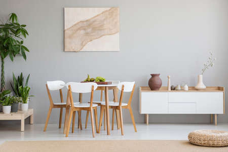Real photo of Scandi dining room interior with vases on cupboard, chairs standing by the table with fresh fruits, poster with textile hanging on wall and plants placed on wooden platform Stock Photo