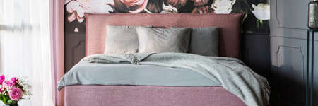 Real photo of dirty pink double bed with grey sheets standing in dark bedroom interior with window with curtains Stock fotó