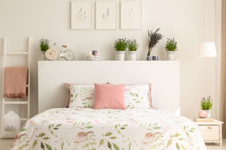 Pink pillow on bed with headboard in white bedroom interior with plants and posters. Real photo Archivio Fotografico - 107997518