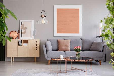 Echtes Foto eines Holzschranks neben einem Sofa in einem modernen Wohnzimmerinnenraum mit einem großen Gemälde