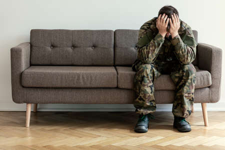 Depressed soldier in green uniform with war syndrome on sofa wainting for therapist 版權商用圖片