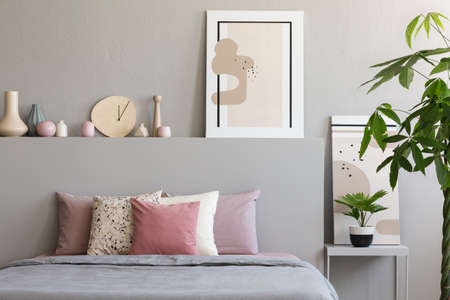 Pastel sheets and cushions placed on double bed in real photo of bedroom interior with paintings, handmade clock and decor Stockfoto