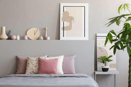 Pastelkleurige lakens en kussens op tweepersoonsbed in echte foto van slaapkamerinterieur met schilderijen, handgemaakte klok en decor Stockfoto