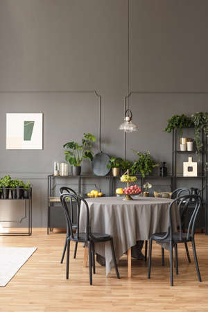 Black Chairs At Round Table Under Lamp In Grey Dining Room Interior With Poster And Plants