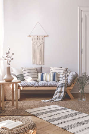 Flowers on table next to wooden sofa with cushions in natural flat interior with pouf. Real photo