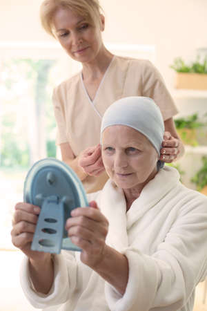 Sick woman with a hair scarf looking at herself in the mirror. Nurse standing in the background