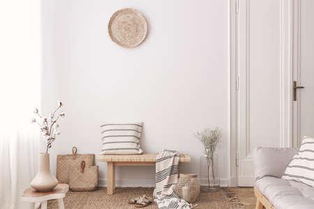 Bloemen op houten tafel in de buurt van bank met kussen en deken in wit woonkamer interieur. Echte foto Stockfoto