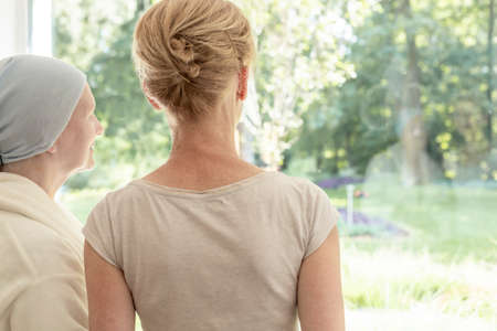 Back of mother with cancer and daughter looking through the window