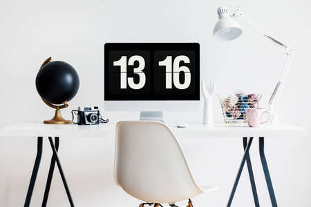 Modern chair by an industrial desk with a computer screen, film camera and decorations in a hipster study space interior with white walls. Real photo.