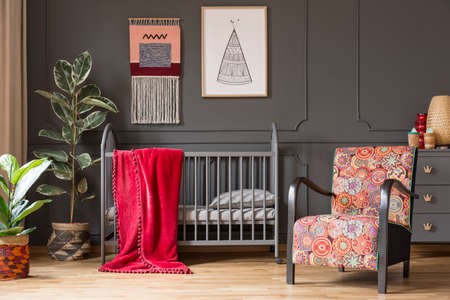Patterned armchair next to babys bed with red blanket in grey bedroom interior with plants. Real photo