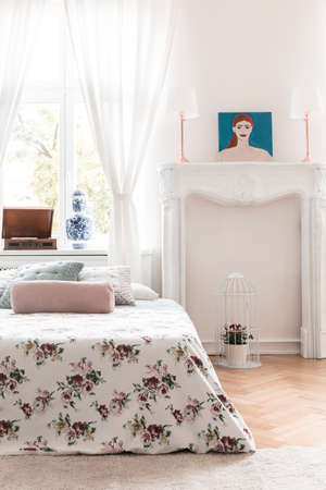 Bed with rose decorated cover and an ornamented fireplace mantel in a high ceiling vintage bedroom interior. Real photo. Stock Photo - 108108370