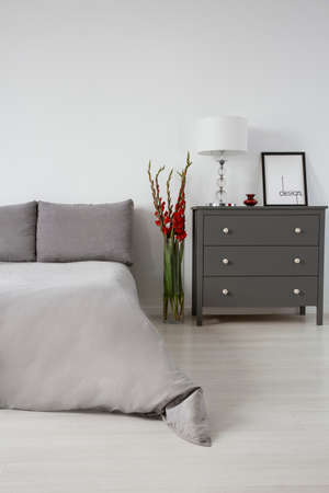 Real photo of a grey bedroom interior with a bed, chest of drawers and red flower. Empty wall, place your painting