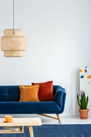 Retro lampshade above a simple, wooden coffee table on a navy blue rug in a colorful living room interior with pillows on a couch. Real photo. Stockfoto - 108108372