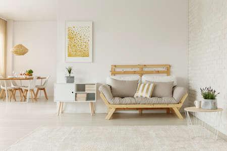 Gouden poster boven witte kast naast beige houten bank in loftinterieur met tafel. Echte foto